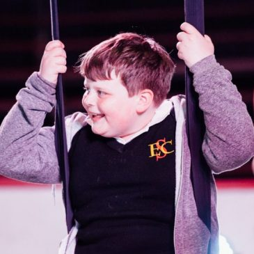 """An image of a little boy smiling as he sways on circus equiptmen"""