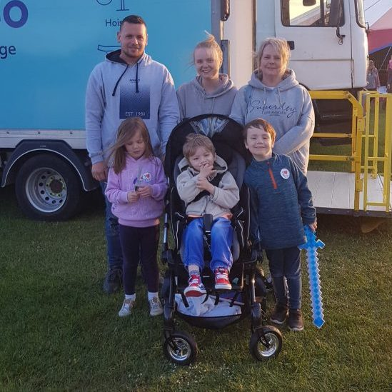 """An image of the family smiling as they stand infront of the changing places facilities on site"""