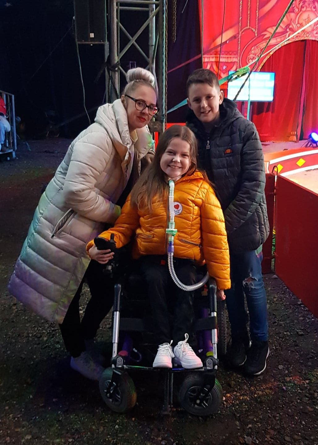 """An image or a Mum, son and daughter at the circus. The young girl is sat in a wheelchair."""