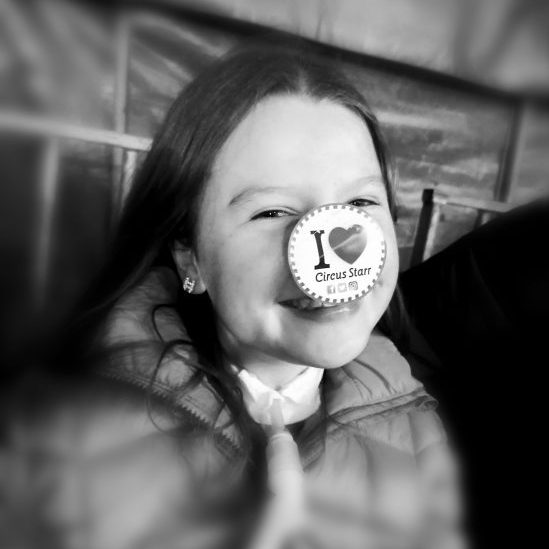 """An image of a little girl smiling, she has an I love circus starr sticker on her nose."""