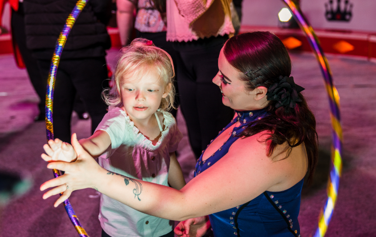 With the help of a circus performer, a young girl is twirling a hoola hoop.