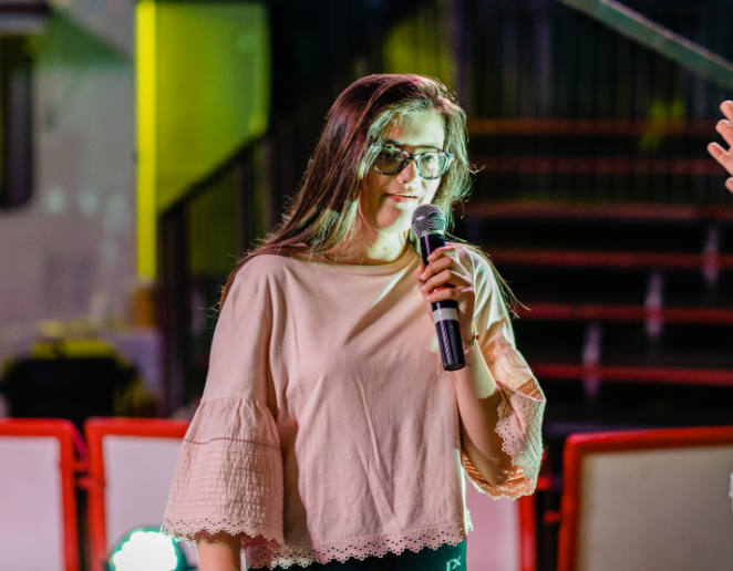 A young girl called Lilly is holding a microphone. She has long brown hair and is wearing glasses.