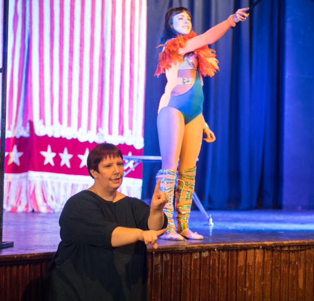 A female performer stands on stage, below here an interpreter is signing in Bitish Sign Language